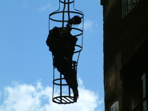 Prisoner in the overhead cage outside the Clink.