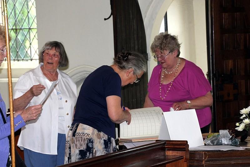 Sheila Rodaway chats with Tricia, Deborah and Irene over the church registers